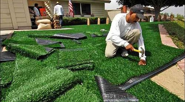 artificial grass installers cutting turf